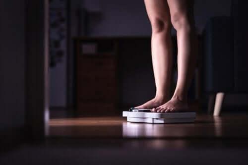 Kilo kaybı ve diyet kavramı: Bir tartı üzerinde duran, kendini tartan bir kadın.