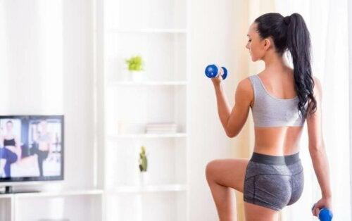 evde küçük ağırlıklarla fitness yapan kadın