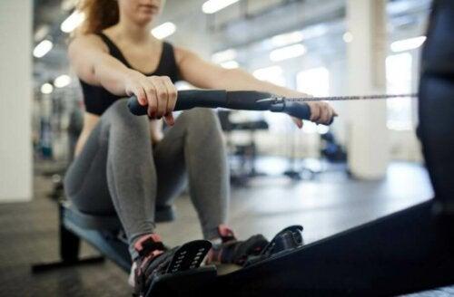 spor salonunda bir kardiyo makinesiyle çalışan sporcu