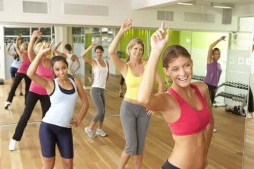 Birkaç kadın spor salonunda zumba dersine katılmış eğleniyorlar.