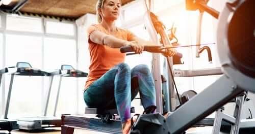 Bir kadın spor salonundaki makinede kürek çekiyor.
