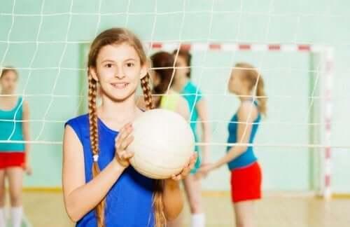 Elinde voleybol topu olan bir kız çocuğu.