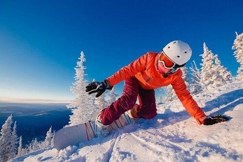 karlı manzarada snowboard yapan sporcu