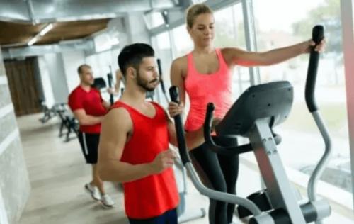 Spor salonunda makineler kullanarak ısınan biri.