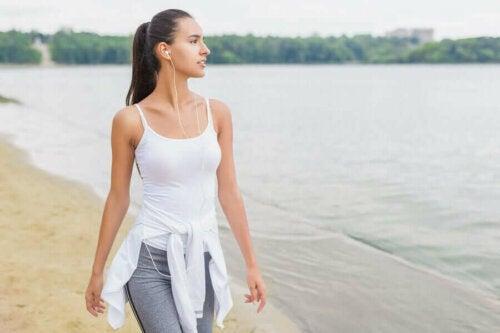 Seyahat sırasında sahilde yürüyüş yapan kadın
