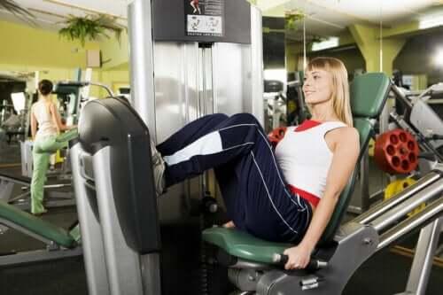 spor salonunda bir spor makinesiyle çalışırken gülümseyen kadın