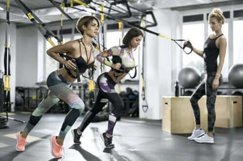 spor salonunda süspansiyon antrenmanı yapan sporcular