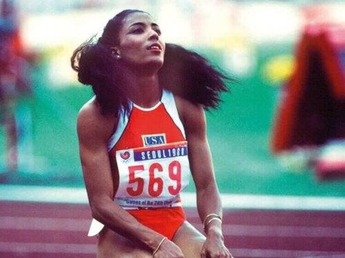 Bir yarıştan sonra yere diz çökmüş Florence Griffith.