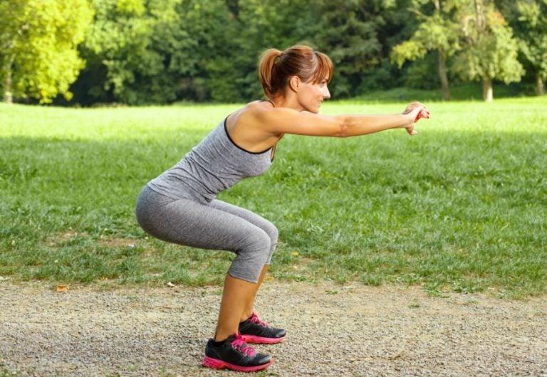 kvinde der laver en squat ude i naturen