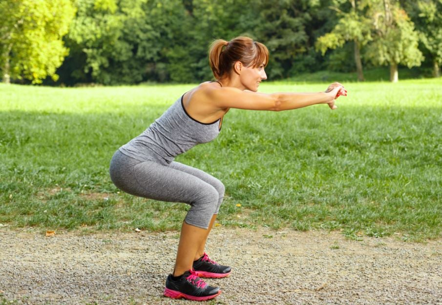 Woman doing squats outdoors