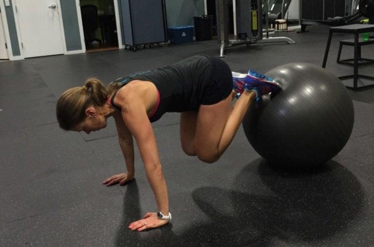 kvinde der laver ball pull in i et fitnesscenter