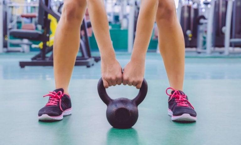 kvinde i fitness der skal til at løfte en kettlebell