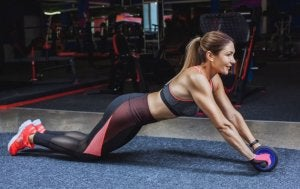 Woman on a routine using the ab wheel.