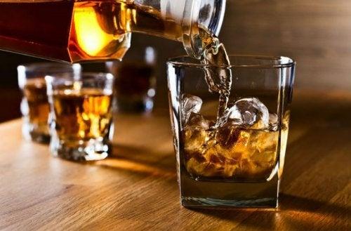whisky der hældes i glas med isterninger