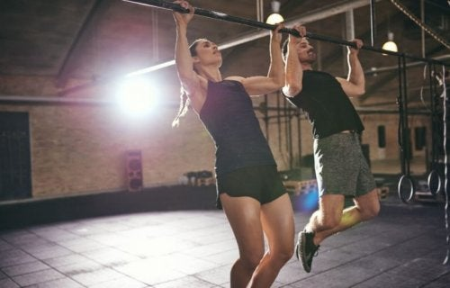 man and woman doing pull-ups at the gym