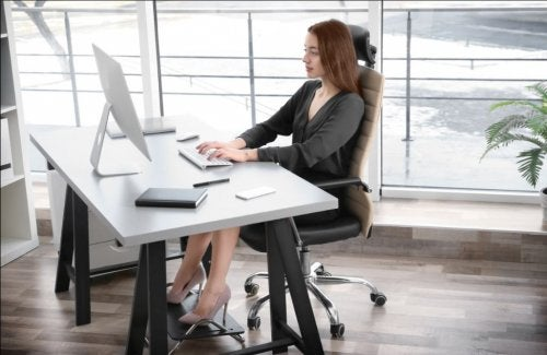 woman working at desk with ergonomic equipment