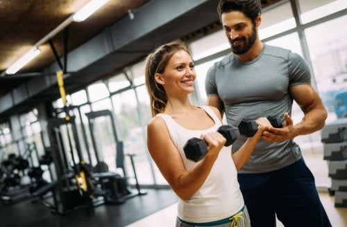 woman lifting dumbbells with trainer