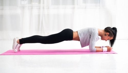 woman doing plank on a mat functional training at home