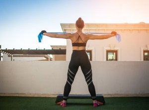 Woman doing resistance band exercise on roof
