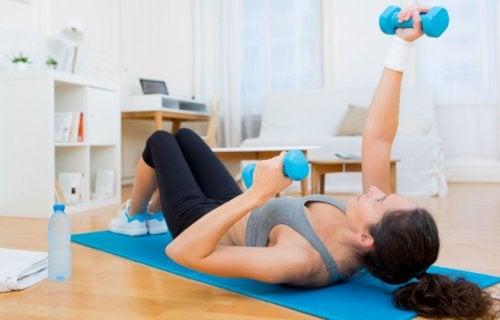 kvinde der laver styrkeøvelse med håndvægte på gulvet