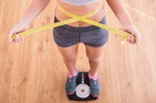 kvinde der står på en vægt og måler sig med målebånd