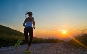 Woman running toward sunset
