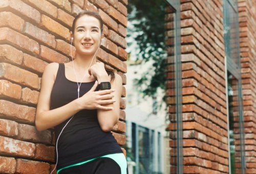 woman in workout gear standing outside with headphones music for running