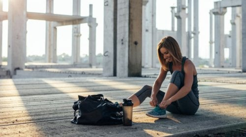 woman smiling tying her shoes exercise regularly