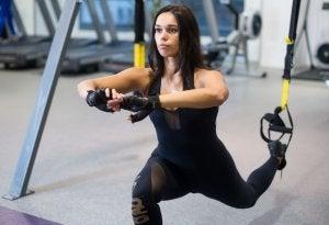 Woman doing Bulgarian split squats with TRX.