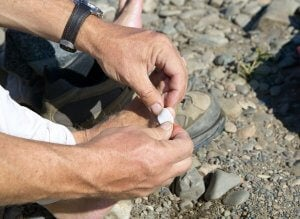 Men putting a bandaid on a blister.