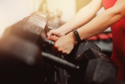 arms with fitness watch reaching for dumbbells
