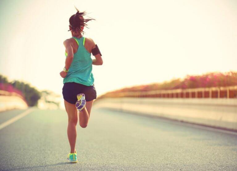 kvinde der løber alene på solskinsrig vej