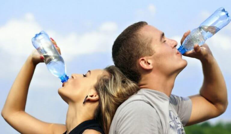 mand og kvinde der drikker vand af flaske