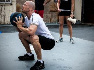 Man using a medicine ball to do squats