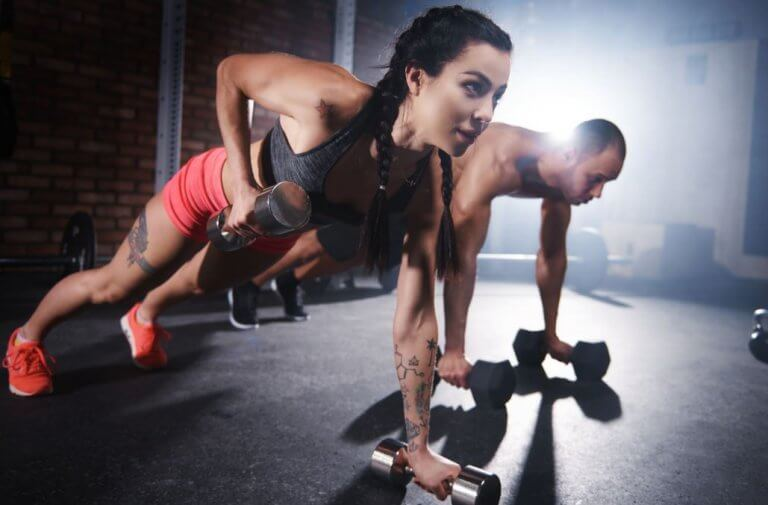 kvinde og mand der laver dumbell rows i planke