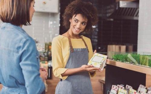 kvinde med forklæde der forklarer om et produkt til en anden kvinde