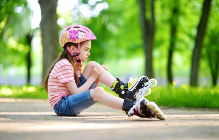 lille pige der sidder på asfalt med rulleskøjter og cykelhjelm på