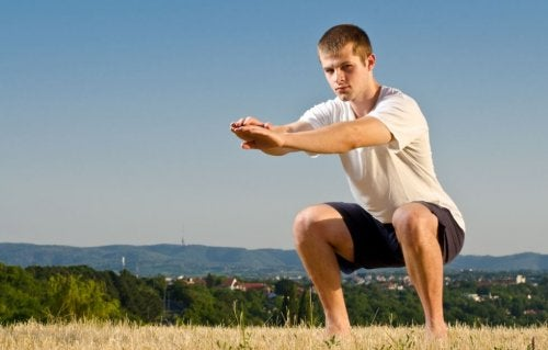 mand der udfører en squat på en mark med en by i baggrunden