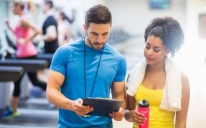 Personal trainer and woman planning routine to avoid overtraining.