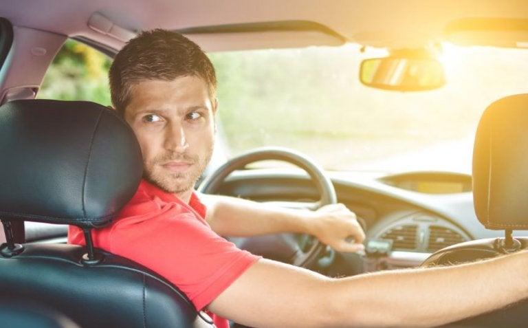 mand der sidder i bil og kigger bagud