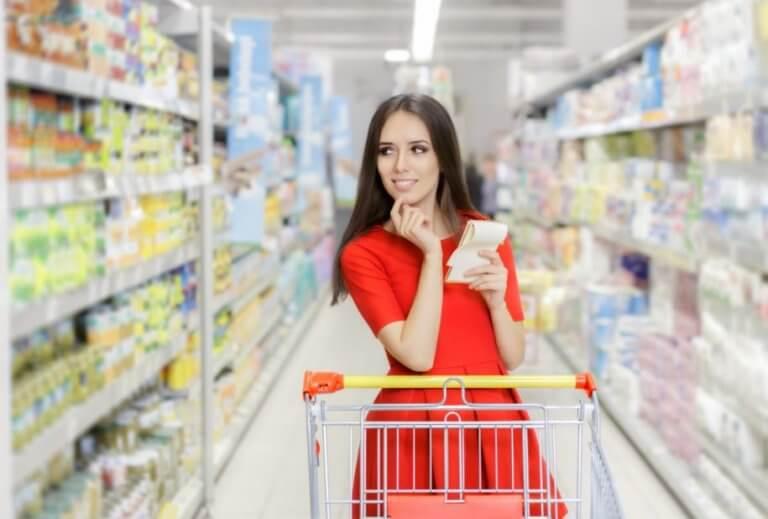 kvinde med indkøbsvogn og liste i supermarked