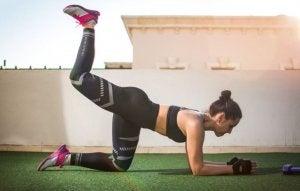 Woman doing an ABT workout outdoors: reverse leg lift.