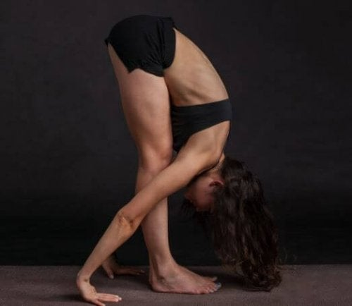 woman on black background doing standing forward bend yoga exercises