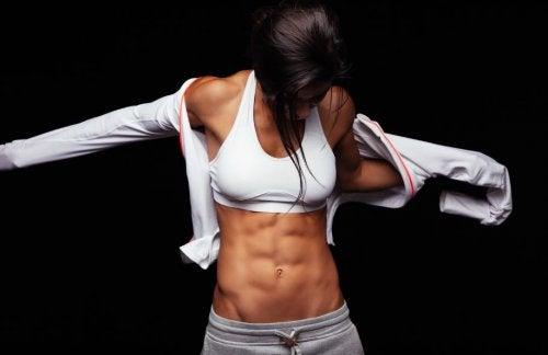 solbrun kvinde med sixpack der tager en hvid træningsbluse på
