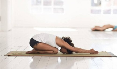 woman doing child pose in well lit yoga studio