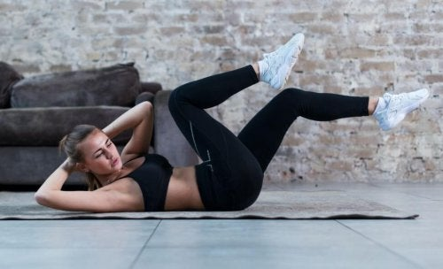 woman doing bicycle crunches exercises to reduce abdominal fat
