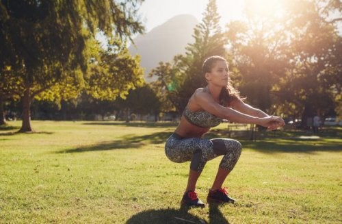 woman squatting outside in workout clothes