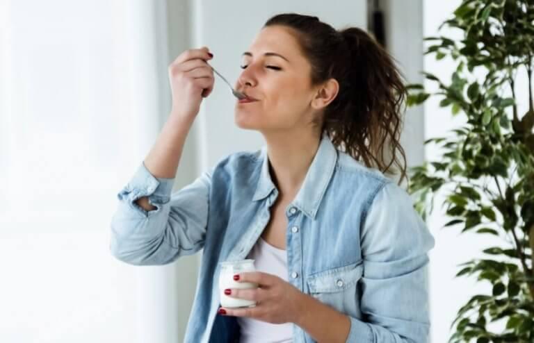 kvinde der nyder en yoghurt
