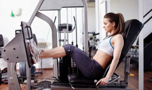 woman at leg press machine at gym toning and bulking up