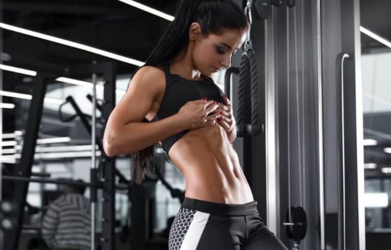 trænet kvinde der hiver op i trøjen og viser sin mave